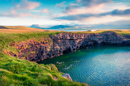 Typical Icelandic landscape with volcanic mountains and Atlantic ocean coast. Sunny summer morning in the west coast of Iceland, Europe. Artistic style post processed photo.