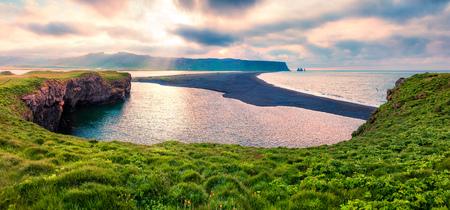 Cloudy summer panorama of Kirkjufjara beach. Beautiful outdoor scene with Reynisdrangar cliffs from Dyrholaey peninsula in Atlantic ocean. South Iceland, Vic village location, Europe.