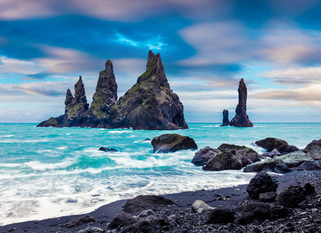 Splendid seascape of Reynisdrangar cliffs in the Atlantic ocean. Colorful summer morning in south Iceland, Vic village location, Europe. Artistic style post processed photo. Фото со стока