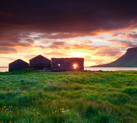 Colorful summer sunset with abandoned buildings near Kirkjufell Mountain in Grundarfjordur town. Evening scene on the Snaefellsnes peninsula, Iceland, Europe. Artistic style post processed photo. Imagens