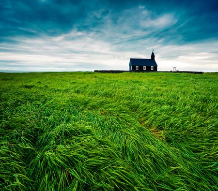 Saefellsnes で黒の木製 Budakirkja 教会。Snafellsnes 半島、西アイスランドは、ヨーロッパに新鮮な緑の芝生のフィールドを持つ劇的な夏の朝。芸術的なス 写真素材