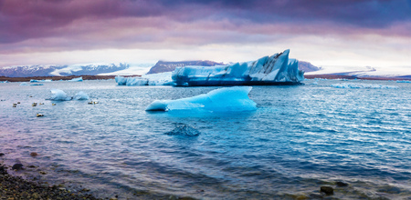 Panorama of floating of blue icebergs in Jokulsarlon glacial lagoon. Colorful sunset in Vatnajokull National Park, southeast Iceland, Europe. Artistic style post processed photo. Stock Photo