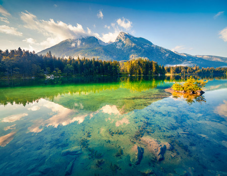 Reflexion of blue sky in the pure water of Hintersee lake. Colorful summer morning in the Austrian Alps, Salzburg-Umgebung district, Austria