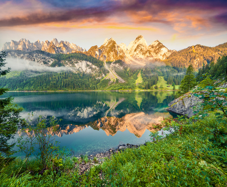 Misty summer morning on the Vorderer Gosausee lake. Colorful sunrise in Austrian Alps, Salzkammergut resort area in the Gosau Valley in Upper Austria Stock Photo