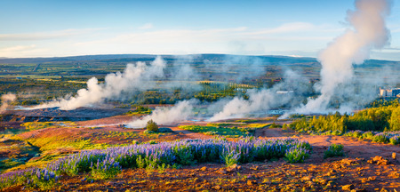 Erupting of the Great Geysir lies in Haukadalur valley on the slopes of Laugarfjall hill. Panorama of foggy summer morning in Southwestern Iceland