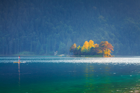Canoeing at summer morning on the Eibsee lake. Splendid outdoor scene in German Alps, Bavaria, Garmisch-Partenkirchen village location, Germany