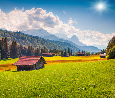 Picturesque view of green meadows near the Kaltenbrunn village with with highest peak of the Wetterstein Mountains, Bavaria, Germany