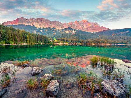 Colorful summer sunrise on the Eibsee lake with Zugspitze mountain range. Splendid outdoor scene in German Alps, Bavaria, Garmisch-Partenkirchen village location, Germany