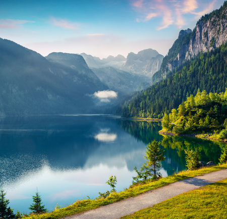Misty summer morning on the Vorderer Gosausee lake with view of Dachstein glacier. Colorful outdoor scene in Austrian Alps, Salzkammergut resort area in the Gosau Valley in Upper Austria