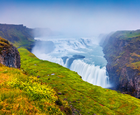 Huge waterfall Gullfoss in the morning mist. Colorful summer scene on Hvita river in southwest Iceland
