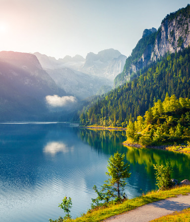 Misty summer morning on the Vorderer Gosausee lake with view of Dachstein glacier. Colorful sunrise Austrian Alps, Salzkammergut resort area in the Gosau Valley in Upper Austria