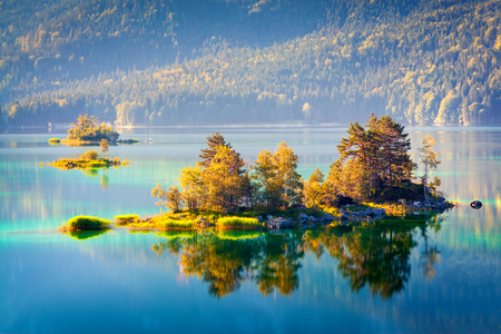 Colorful islang glowing by sunlight on the Eibsee lake. Splendid outdoor scene in German Alps, Bavaria, Garmisch-Partenkirchen village location, Germany