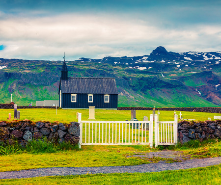 Black wooden Budakirkja church at Saefellsnes. Dramatic summer morning with field of fresh green grass on Snafellsnes peninsula, western Iceland