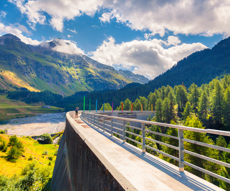 Photographer takes a photo on the dam on Orlegna river. Sunny summer view from the top of Maloja pass. Swiss Alps, Upper Engadine in canton of the Grisons, Switzerland