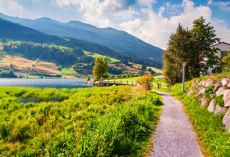 Colorful summer view of St. Valentin village. Morning outdoor scene of Muta lake (Haidersee), South Tyrol, Italy