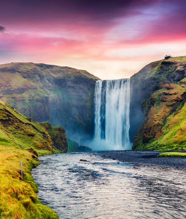 Unbelievable summer view of Skogafoss Waterfall on Skoga river. Colorful summer sunrise in Iceland, Europe. Artistic style post processed photo.