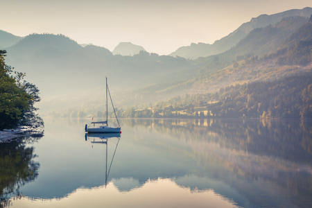Misty morning scene on Grundlsee lake with yacht. Beautiful summer sunrise in Gessl village, Liezen District of Styria, Austria, Alps. Europe. Artistic style post processed photo.