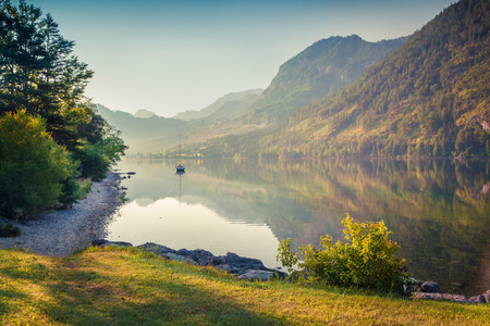 Colorful morning scene on Grundlsee lake with yacht. Beautiful summer sunrise in Gessl village, Liezen District of Styria, Austria, Alps. Europe. Artistic style post processed photo.