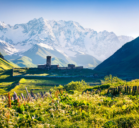Colorful summer scene with ancient Lamaria church in Ushguli village. Majestic morning view of Shkhara mountains in Upper Svaneti. Caucasus mountains, Georgia, Europe. Artistic style post processed photo.