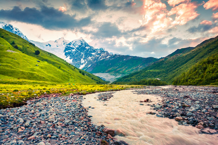 Colorful summer sunrise in the mountain valley with Adishchala river. Majestic morning view of Shkhara Mountain in Caucasus mountains, Upper Svaneti, Adishi village location, Georgia, Europe.  Stock Photo