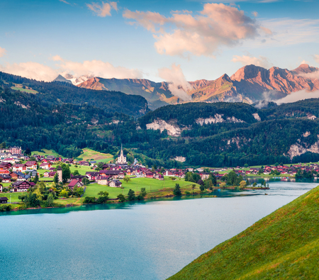 Misty summer view of Lungerersee lake. Colorful morning scene in Swiss Alps, Lungern village location, Switzerland, Europe. Artistic style post processed photo. Stock Photo