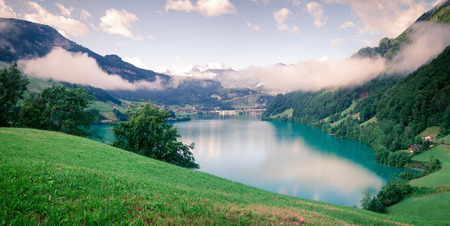 Foggy summer panorama of Lungerersee lake. Colorful morning view of Swiss Alps, Lungern village location, Switzerland, Europe.