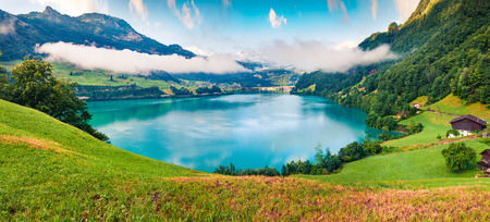 Foggy summer panorama of Lungerersee lake. Colorful morning view of Swiss Alps, Lungern village location, Switzerland, Europe. Artistic style post processed photo.