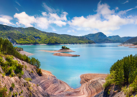 Colorful summer landscape on the Serre-Poncon lake. Sunny morning view of the French Alps, Les Bernards village location, Hautes-Alpes department,  southeastern France, Europe.
