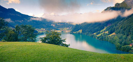 Foggy summer panorama of Lungerersee lake. Colorful morning view of Swiss Alps, Lungern village location, Switzerland, Europe. Green filter toned. Stock Photo - 89423741