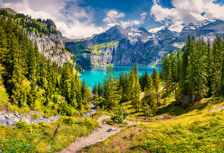 Picturesque summer view of unique Oeschinensee Lake. Sunny morning scene in the Swiss Alps with Bluemlisalp mountain, Kandersteg village location, Switzerland, Europe. Stock Photo - 89423867