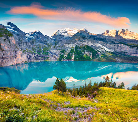 Colorful summer sunrise on the unique Oeschinensee Lake. Splendid morning scene in the Swiss Alps with Bluemlisalp mountain, Kandersteg village location, Switzerland, Europe.