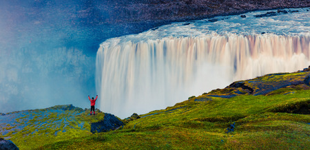 Tourist standing on the shore of falling water of the most powerful waterfall in Europe - Dettifoss with raised hands. Colorful summer sunset in Jokulsargljufur National Park, Iceland. White nights view.