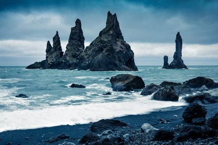 Dramatic seascape of Reynisdrangar cliffs in the Atlantic ocean. dark summer morning on south Iceland, Vik village location, Europe. Artistic style post processed photo.