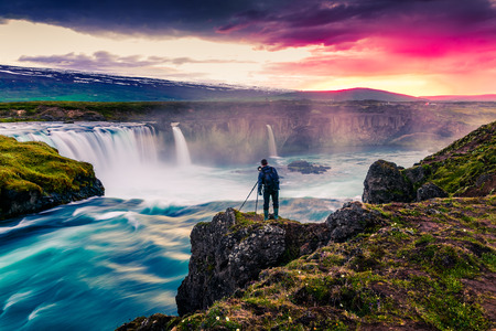 Summer morning scene on the Godafoss Waterfall with photographer. Colorful sunrise on the on Skjalfandafljot river, Iceland, Europe. Artistic style post processed photo.