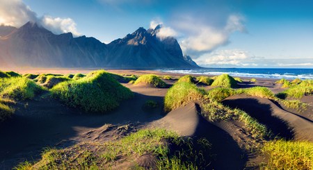 Black sand dunes on the Stokksnes headland on southeastern Icelandic coast with Vestrahorn (Batman Mountain). Colorful summer morning Iceland, Europe. Beauty of nature concept background.