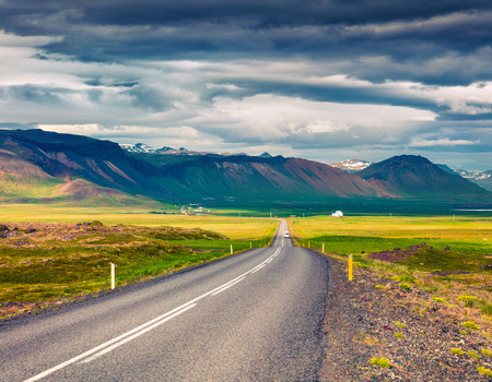 Empty asphalt road with colorful cloudy sky. Beautiful outdoor scenery in Iceland, Europe. Beautiful outdoor scenery in Iceland, Europe. Image of travel concept background.