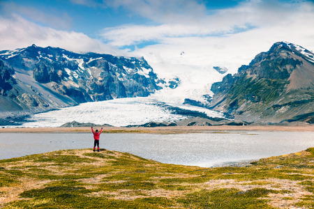 Melting ice from Vatnajokull glacier. Sunny summer landscape with man standing on the shore with raised hands, Vatnajokull National Park, Iceland, Europe. Artistic style post processed photo. Stock Photo - 91319691