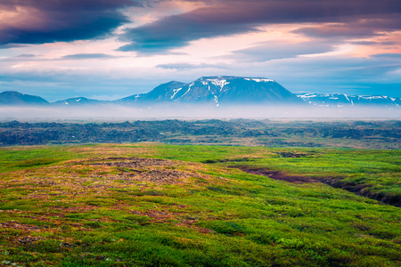 Typical Icelandic landscape with foggy mountains on the horizon. Colorful summer sunrise near the Myvatn lake located, Iceland, Europe. Artistic style post processed photo.