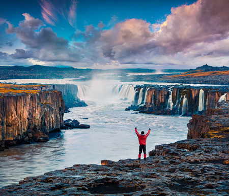Tourist standing on the standing on the edge of Jokulsa a Fjollum river with raised hands and enjoying sunrise. Colorful summer scene on the Selfoss Waterfall in Jokulsargljufur National Park, Iceland.