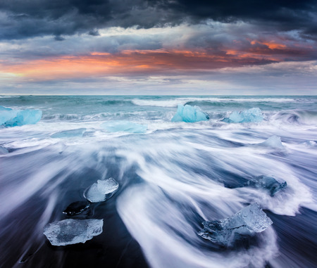 Blocks of ice washed by the waves on Jokulsarlon beach. Dramatic summer sunrise in Vatnajokull National Park, southeast Iceland, Europe.Artistic style post processed photo. Stock Photo