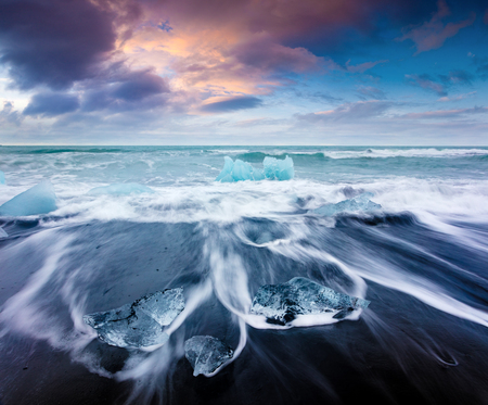 Blocks of ice washed by the waves on Jokulsarlon beach. Dramatic summer sunrise in Vatnajokull National Park, southeast Iceland, Europe.Artistic style post processed photo.