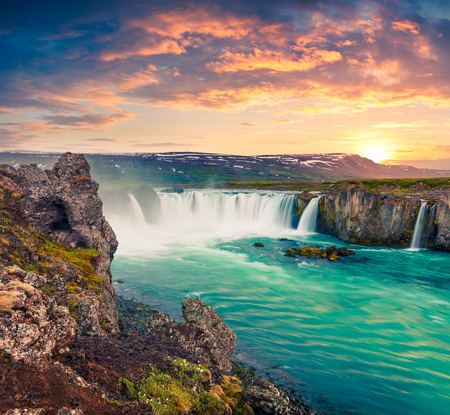 Picturesque summer morning scene on the Godafoss Waterfall. Colorful sunrise on the on Skjalfandafljot river, Iceland, Europe. Artistic style post processed photo.