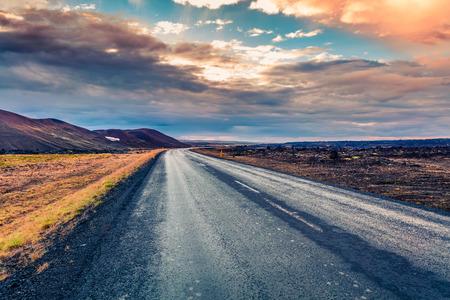 カラフルな曇り空と空のアスファルト道。Hverarond 地熱谷、アイスランド、ヨーロッパの美しい屋外風景。旅行の概念の背景のイメージ