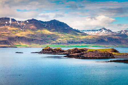 Typical Icelandic landscape with volcanic mountains and Atlantic ocean coast. Sunny summer view of the the north coast of Iceland, Europe. Artistic style post processed photo.