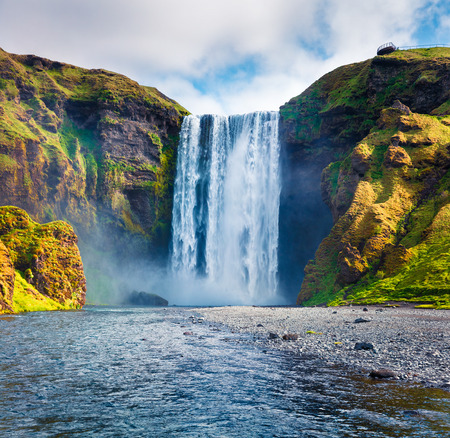 Splendid summer view of huge Skogafoss Waterfall on Skoga river. Colorful summer scene in south Iceland, Europe. Artistic style post processed photo.