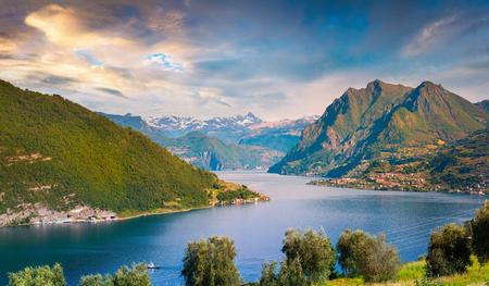Alba variopinta di estate sul lago Iseo. Veduta aerea del villaggio di Zorzino. Grande scena del mattino nelle Alpi, in Italia, in Europa. Bellezza del fondo di concetto di campagna.