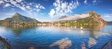 Sunny spring pznorama of the Como lake. Bright morning scene in the Lecco town. Beautiful misty landscape in Alp mountains, Italy, Europe.