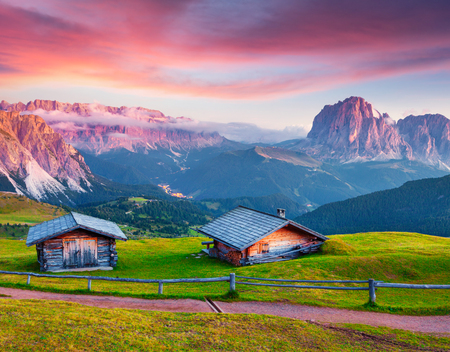 Colorful summer sunrise on the Sassolungo (Langkofel) and Sella group. Amazing morning view of Gardena valley, National Park Dolomites, Ortisei village location, S. Cristina and Selva, Italy, Europe.