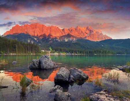 Eibsee 호수에 극적인 여름 석양. 독일 알프스에서 화려한 저녁 장면입니다. 바바리아, 독일, 유럽. 자연 컨셉 배경의 아름다움입니다. 예술적 스타일 게 스톡 콘텐츠