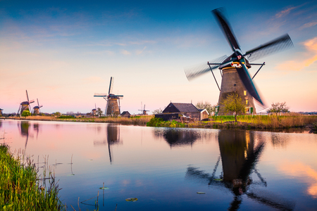 Famous mindmills in Kinderdijk museum in Holland. Colorful spring sunset in countryside. Splendid outdoor scene in Netherlands, Europe. Artistic style post processed photo.
